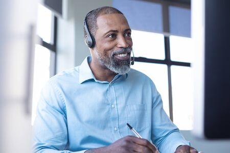 Vorderansicht, Nahaufnahme eines afroamerikanischen männlichen Geschäfts, der in einem zwanglosen modernen Büro arbeitet, Notizen macht, lächelt und über ein Telefon-Headset spricht Standard-Bild