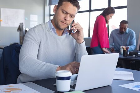 Front view close up of a Caucasian male business creative working in a casual modern office, using a laptop and talking on his smartphone, with colleagues in the background