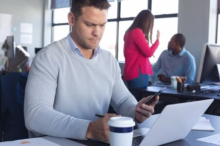 Vista frontale ravvicinata di un business creativo maschio caucasico che lavora in un ufficio moderno e casual, usando un laptop e guardando il suo smartphone, con i colleghi sullo sfondo