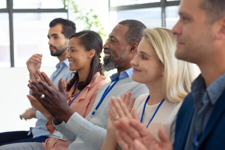 Side view of a diverse group of business creatives sitting in a row in the audience at a business conference clapping