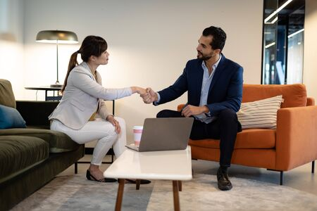 Side view of an Asian businesswoman and mixed race businessman sitting in the lobby of a modern office with a laptop computer, shaking hands and talking