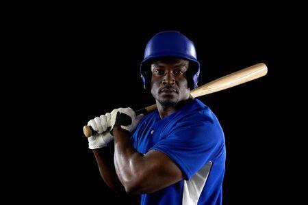 Portrait of an African American male baseball player, a hitter, wearing a team uniform and a helmet, ready to swing a baseball bat