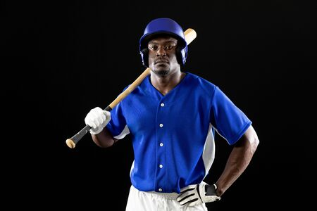 Portrait of an African American male baseball player, a hitter, wearing a team uniform and a helmet, holding a baseball bat on his shoulder, his hand on his hip