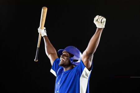 Side view of an African American male baseball player, a hitter wearing a team uniform, a helmet and holding a baseball bat, with arms raised in celebration of a victory