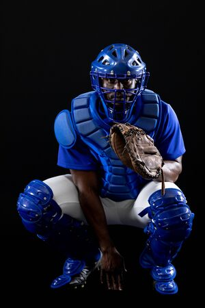 Front view of an African American male baseball player, a catcher, wearing a team uniform, protective clothing, a helmet and a mitt, ready for a pitch