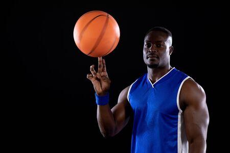 Vista frontale di un muscoloso giocatore di basket maschio afroamericano che indossa i colori della squadra che gira una palla da basket sulla punta del dito e guarda la telecamera