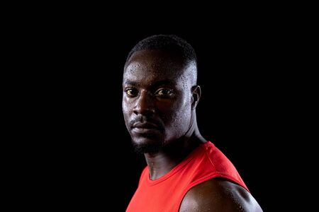 Portrait close up of an African American male athlete wearing sports clothes sweating after a work out, head turned and looking to camera. On a black background