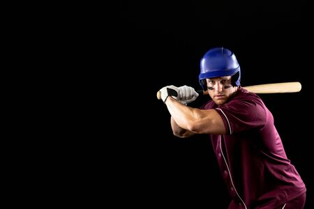 Front view of a Caucasian male baseball player, a hitter, wearing a team uniform and a helmet, stripes of eye black under his eyes, ready to swing a baseball bat 스톡 콘텐츠