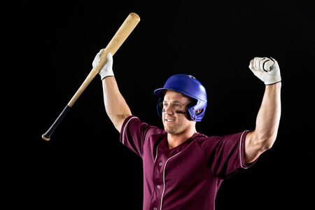 Front view of a Caucasian male baseball player, a hitter, wearing a team uniform, a helmet and holding a baseball bat, with arms raised in celebration of a victory. Vertical shot 스톡 콘텐츠