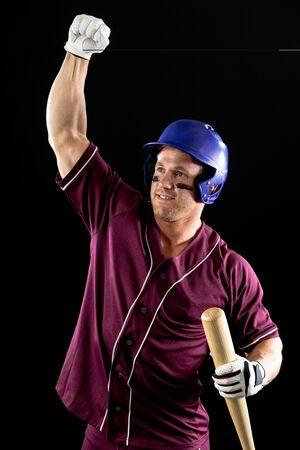 Vista frontal de cerca de un jugador de béisbol masculino caucásico, un bateador con uniforme de equipo, un casco y sosteniendo un bate de béisbol, con el puño levantado en celebración de una victoria. Tiro vertical