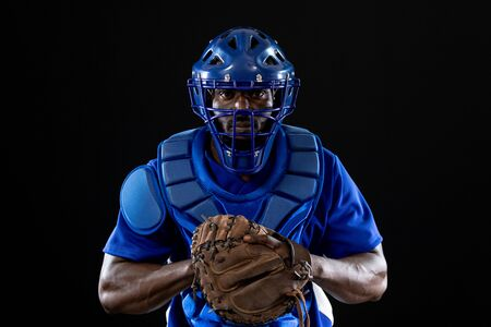 Front view of an African American male baseball player, a catcher, wearing a team uniform, protective clothing, a helmet and a mitt, ready for a pitch Stock fotó