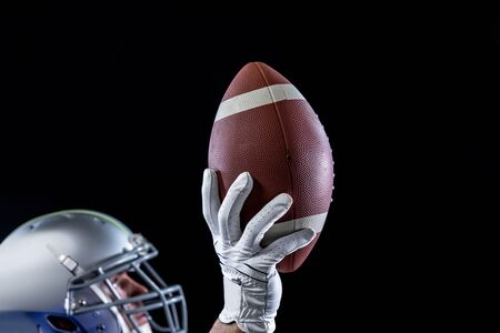 Side view of a Caucasian male American football playing wearing a helmet looking up and holding a football in one gloved hand