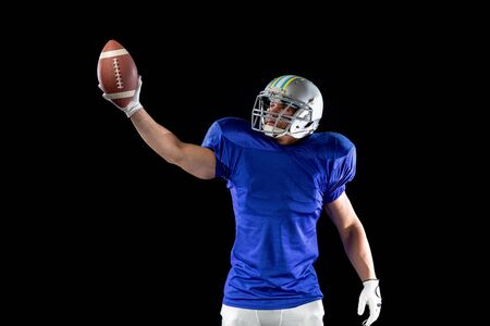 Front view of a Caucasian male American football player wearing a team uniform, pads and a helmet, holding a football in one raised hand and looking up at it