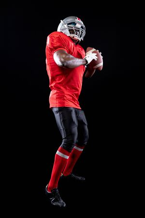 Side view close up of an African American male American football player wearing a team uniform, pads and a helmet, holding a football in both hands