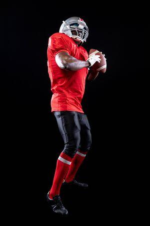 Vista laterale ravvicinata di un giocatore di football americano maschio afroamericano che indossa un'uniforme della squadra, imbottiture e un casco, con in mano un pallone da calcio con entrambe le mani