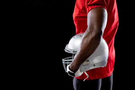Vista laterale a metà sezione di un giocatore di football americano maschio afroamericano che indossa un'uniforme della squadra, imbottiture e guanti, tenendo un casco sotto il braccio