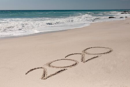 2020 written in the sand on a sunny beach with calm sea and clear blue sky, , new year and new years eve concept Stock Photo