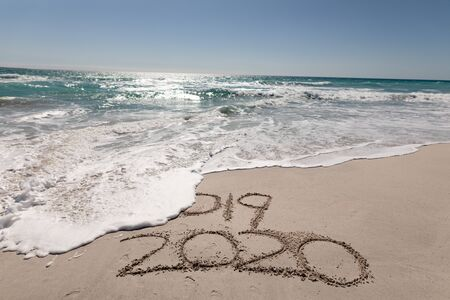 2019 and 2020 written in the sand on a sunny beach with calm sea and clear blue sky, the tide washing away the year 2019, new year and new years eve concept