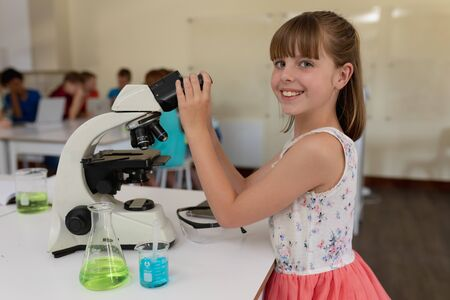 Portrait of a Caucasian elementary school girl at a desk using a microscope during a science class smiling to camera, a flask and a beaker of colourful liquids on the desk beside her, with classmates working together sitting at a table in the background