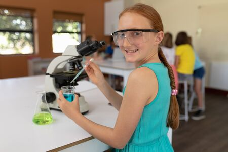 Portrait of a Caucasian elementary school girl with red hair in a plait wearing safety glasses and a blue t shirt, at a desk using a pipette and a beaker, turning and smiling to camera during a science class, with classmates working together sitting at a table in the background