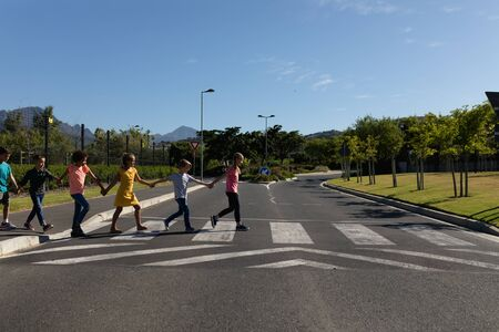 Side view of a diverse group of elementary school pupils crossing an empty road together, half way across a pedestrian crossing, holding hands on a sunny day Stock Photo