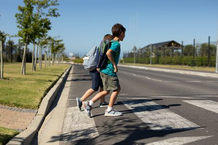 Side view of two Caucasian schoolboys crossing the road on a pedestrian crossing on their way to elementary school on a sunny day