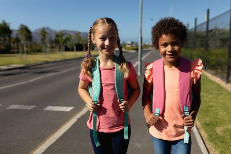 Portrait of a Caucasian and an African American schoolgirl walking along a road to elementary school together in the sun, smiling to camera