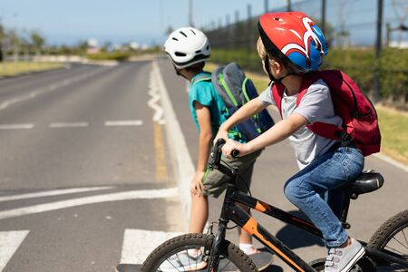 Side view close up of two Caucasian school boys wearing cycling helmets looking away from camera for traffic and waiting on a pedestrian crossing to cross the road, one on a skateboard and one riding a bicycle, on their way to elementary school on a sunny day