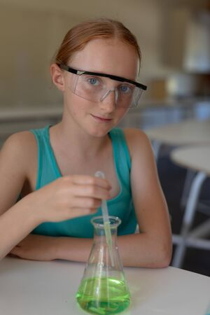 Portrait close up of a Caucasian elementary school girl sitting at a table wearing safety glasses, looking to camera and smiling, using a pipette and a beaker to do an experiment during a chemistry lesson Banco de Imagens