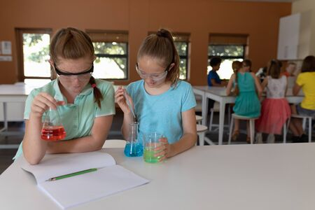 Front view of two Caucasian schoolgirls sitting at a desk wearing safety glasses and using flasks of colourful liquid while doing an experiment during an elementary school science class
