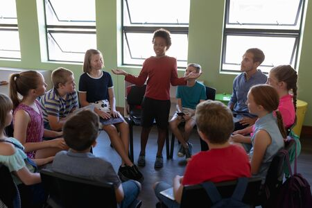 Front view of a diverse group of elementary school kids sitting on chairs in a circle and interacting during a lesson, one African American girl standing and talking while her classmates and male Caucasian teacher sit and listen