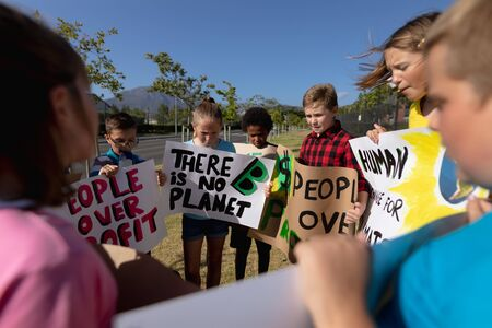 Over the shoulder view of a diverse group of elementary school pupils on a protest march, carrying signs with environmental and conservation slogans on them, walking down a road in the sun