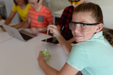 Side view close up of a Caucasian girl wearing safety glasses and a green t shirt, sitting at a desk using a pipette and a beaker, turning and smiling to camera during an elementary school science class, with classmates working together sitting at a table using a laptop and a tablet computer in the background