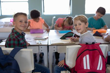 Side view of two Caucasian schoolboys sitting at desks in an elementray school classroom writing in their notebooks turning to smile to camera, with their clasmates working at desks in the background