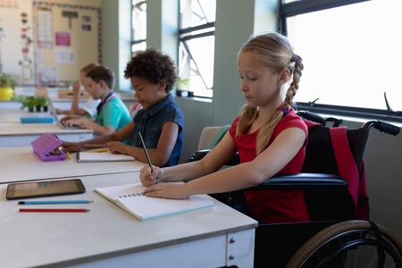 Side view of a Caucasian schoolgirl with blonde hair in plaits sitting in a wheelchair and sitting at a desk writing, with a diverse group of schoolchildren sitting at desks beside her working in an elementary school classroom Zdjęcie Seryjne
