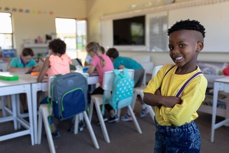 Portrait of an African American schoolboy with short hair wearing a yellow shirt, standing with arms crossed and looking to camera smiling in an elementary school classroom, with classmates sitting at desks working in the background