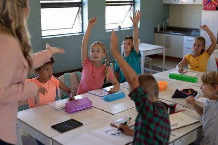 Front view of a diverse group of schoolchildren sitting at tables in an elementary school classroom raising their hands to answer a Caucasian female teacher with long blonde hair, standing in the foreground, focus on the background Banco de Imagens