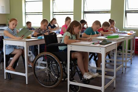 Side view of a diverse group of schoolchildren sitting at desks writing during a lesson in an elementary school classroom, with one Caucasian schoolgirl sitting in a wheelchair in the foreground