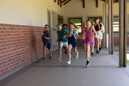 Front view of a diverse group of schoolchildren wearing shorts, skirts and rucksacks running in an outdoor corridor at elementary school