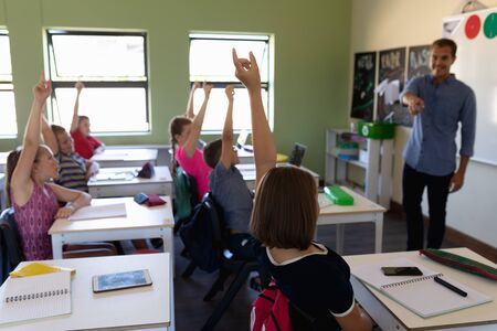 Front view of a Caucasian male school teacher standing in front of a diverse group of school children sitting at desks and raising their hands to answer a question during a lesson in an elementary school classroom, the teacher pointing to one of them to answer