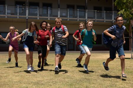 Front view of a diverse group of schoolchildren wearing shorts and rucksacks running in a playing field at elementary school and looking to camera smiling