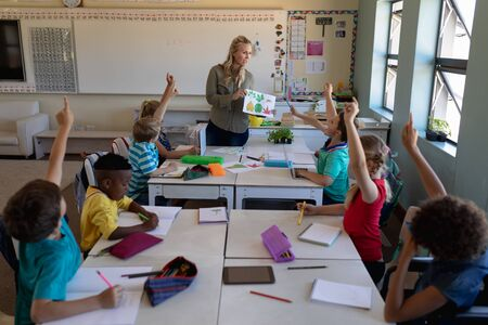 High angle view of a Caucasian female teacher with long blonde hair holding a picture of leaves and a diverse group of schoolchildren sitting at desks looking and raising their hands, during a lesson in an elementary school classroom
