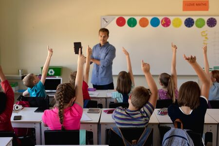 Vooraanzicht van een blanke mannelijke schoolleraar die voor de klas staat met een tabletcomputer en een diverse groep schoolkinderen toespreekt, aan een bureau zit en hun hand opsteekt om een vraag te beantwoorden tijdens een les in een klaslokaal op de basisschool