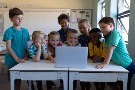 Front view of a diverse group of eight schoolchildren gathered around two desks using a laptop computer together in an elementary school classroom and smiling Banque d'images