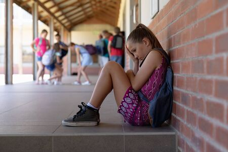 Side view of a Caucasian schoolgirl wearing a purple dress and a rucksack sitting on the ground against a wall alone in the schoolyard at elementary school looking sad, with other schoolchildren standing together in the background Banco de Imagens