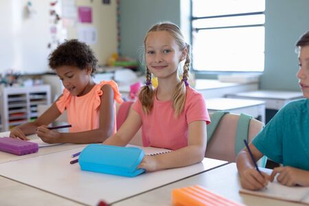 Front view of a Caucasian schoolgirl with blonde plaits wearing a pink t shirt sitting at a desk and smiling to camera during a lesson in an elementary school classroom, an African American schoolgirl and a Caucasian schoolboy sitting on either side of her writing in their notebooks