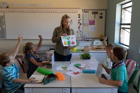 Front view of a Caucasian female teacher with long blonde hair holding a picture of leaves and a diverse group of schoolchildren sitting at desks looking and raising their hands, during a lesson in an elementary school classroom