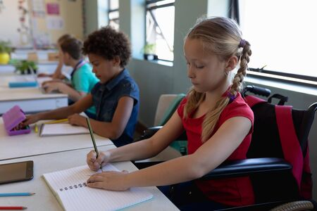 Side view close up of a Caucasian schoolgirl with blonde hair in plaits sitting in a wheelchair and sitting at a desk writing, with a diverse group of schoolchildren sitting at desks beside her working in an elementary school classroom