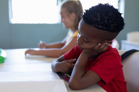 Side view of an African American schoolboy with short hair wearing a red t shirt, sitting at a desk resting his head on his hand and looking at his book during a lesson in an elementary school classro