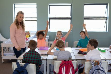 Front view of a Caucasian female elementary school teacher with long blonde hair standing in a classroom talking to a Caucasian schoolboy during a lesson, while a diverse group of his classmates sitting at desks listen and raise their hands to answer a question Banco de Imagens